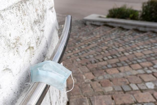 Na poręczy schodów w parku miejskim leży zapomniana medyczna maska na twarz.