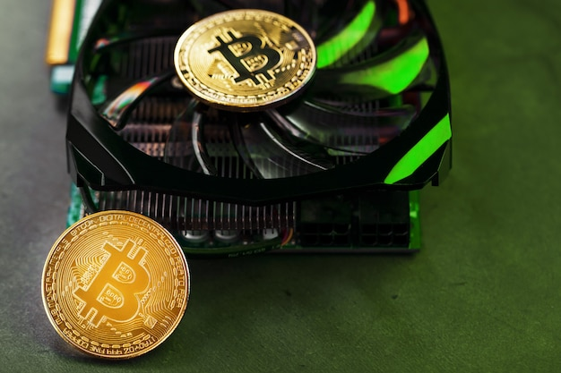 Na potężnych fanach karty graficznej znajdują się monety kryptowaluty bitcoin z zielonym podświetleniem. koncepcja kopania i kopania kryptowaluty na farmę kryptowalut. makro