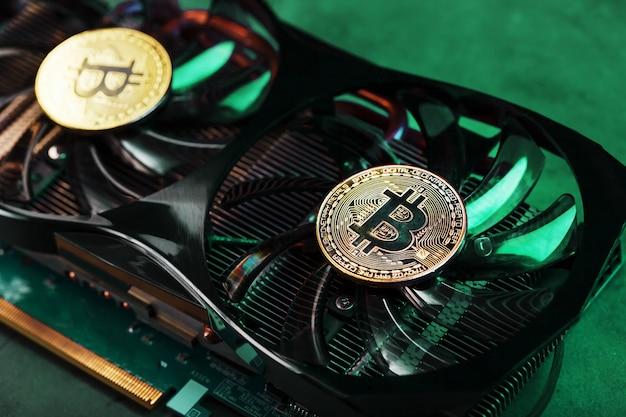 Na potężnych fanach karty graficznej znajdują się monety kryptowaluty bitcoin z zielonym podświetleniem