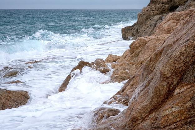 Na przybrzeżnych skałach rozbijają się spienione fale morskie. morski krajobraz naturalny