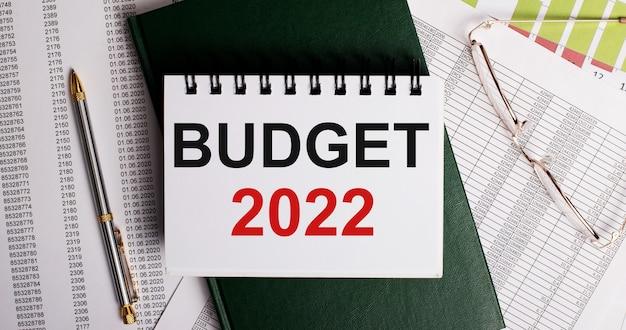 Na pulpicie raporty, okulary, długopis, zielony pamiętnik i biały notatnik z napisem budżet 2022