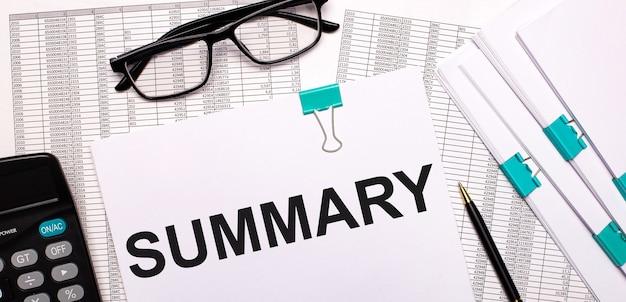 Na pulpicie są raporty, dokumenty, okulary, kalkulator, długopis i kartka z napisem podsumowanie