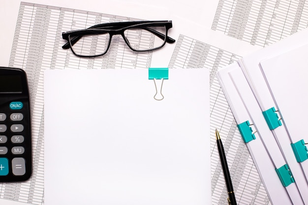 Na pulpicie są raporty, kalkulator, okulary, stosy papierów i czysty biały papier do wstawienia tekstu