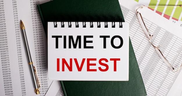 Na pulpicie są raporty, okulary, długopis, zielony pamiętnik i biały notatnik z napisem time to invest. zbliżenie w miejscu pracy. pomysł na biznes