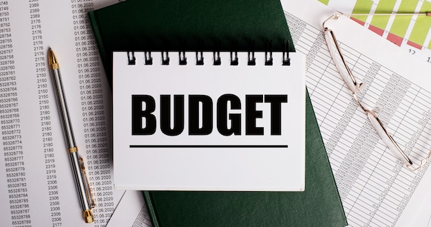 Na pulpicie są raporty, okulary, długopis, zielony pamiętnik i biały notes z napisem budżet. zbliżenie w miejscu pracy. pomysł na biznes