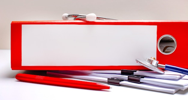 Na pulpicie stetoskop, długopis, czerwona teczka z plikami z miejscem na wstawienie tekstu. koncepcja medyczna