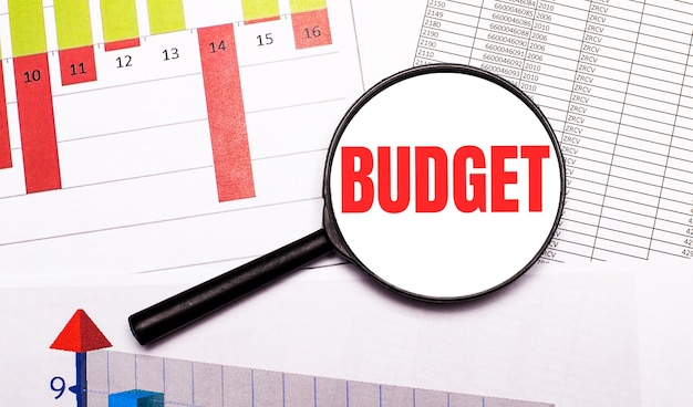 Na pulpicie wykresy, raporty, lupa z napisem budżet. pomysł na biznes