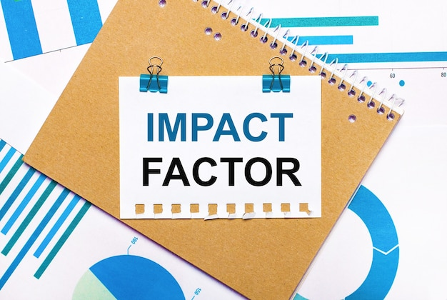 Na pulpicie znajdują się niebiesko-jasnoniebieskie wykresy i diagramy, brązowy notatnik i kartka papieru z niebieskimi spinaczami i napisem impact factor. widok z góry. pomysł na biznes