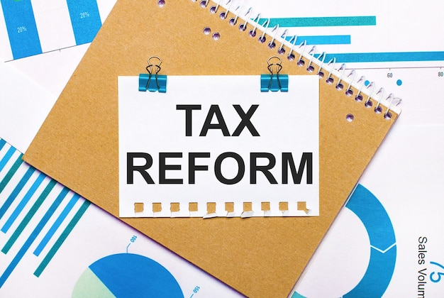 Na pulpicie znajdują się niebiesko-jasnoniebieskie wykresy i diagramy, brązowy notatnik i kartka papieru z niebieskimi spinaczami i tekstem reformy podatkowej.