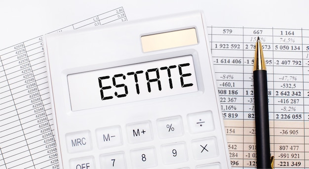 Na pulpicie znajdują się raporty, biały kalkulator z napisem estate na tablicy wyników oraz długopis. pomysł na biznes.