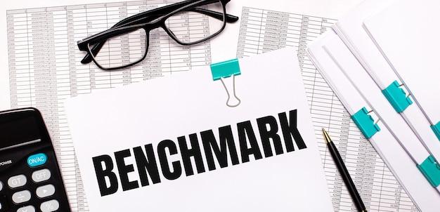 Na pulpicie znajdują się raporty, dokumenty, okulary, kalkulator, długopis i papier z napisem benchmark. pomysł na biznes