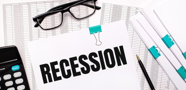 Na pulpicie znajdują się raporty, dokumenty, okulary, kalkulator, długopis i papier z napisem recesja. pomysł na biznes