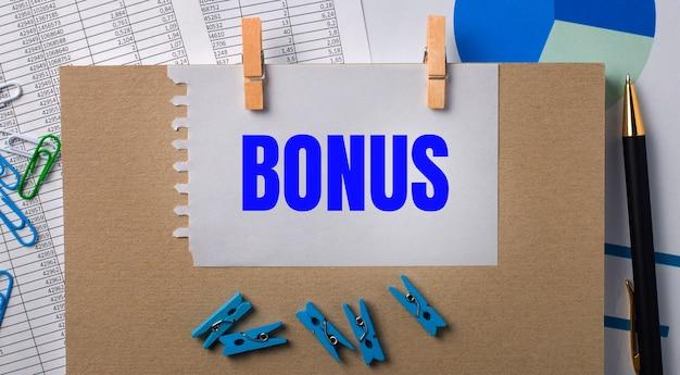 Na pulpicie znajdują się raporty, niebieskie spinacze do bielizny i wykresy, długopis, notatnik i kartka papieru z tekstem bonus. pomysł na biznes