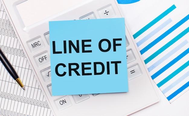 Na pulpicie znajduje się biały kalkulator z niebieską naklejką z napisem linia kredytowa, długopis i niebieskie raporty. pomysł na biznes
