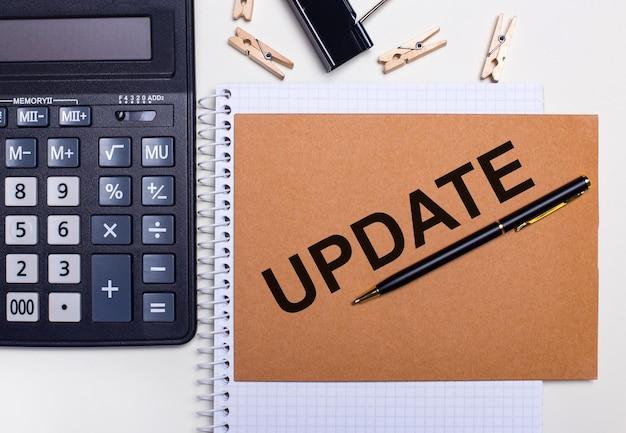 Na pulpicie znajduje się kalkulator, długopis i spinacze do bielizny obok notatnika z napisem update. pomysł na biznes. widok z góry