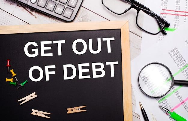 Na pulpicie znajduje się kalkulator, raporty, okulary, lupę, długopisy oraz tablica z spinaczami do bielizny i tekstem wyjdź z długów.koncepcja biznesowa.