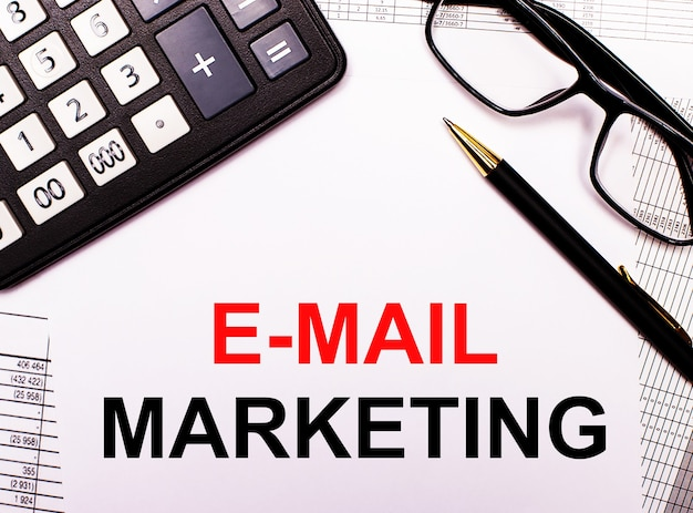 Na raportach kalkulator, okulary, długopis i notes z napisem e-mail marketing