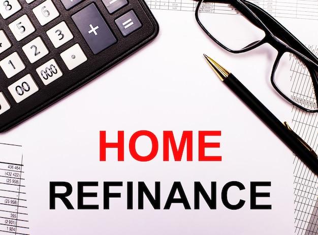 Na raportach kalkulator, okulary, długopis i notes z napisem home refinance