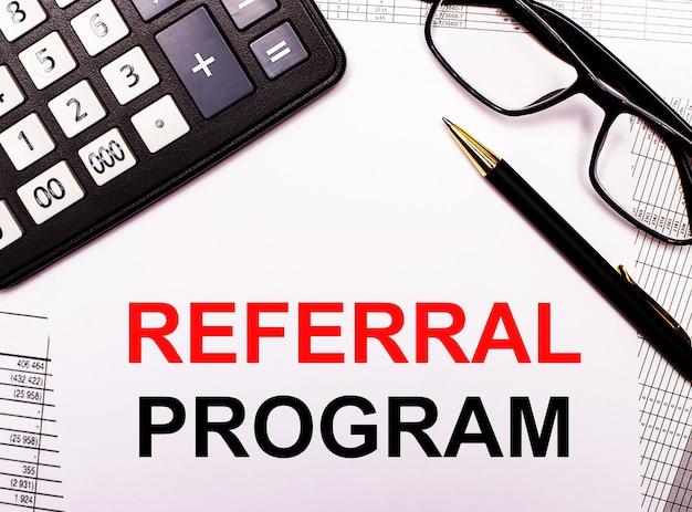 Na raportach znajduje się kalkulator, okulary, długopis oraz notes z napisem referral program.