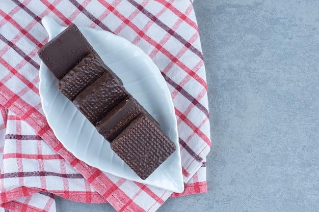 Na ręczniku, na marmurowym stole miska czekolady pokryta chrupiącym wafelkiem.