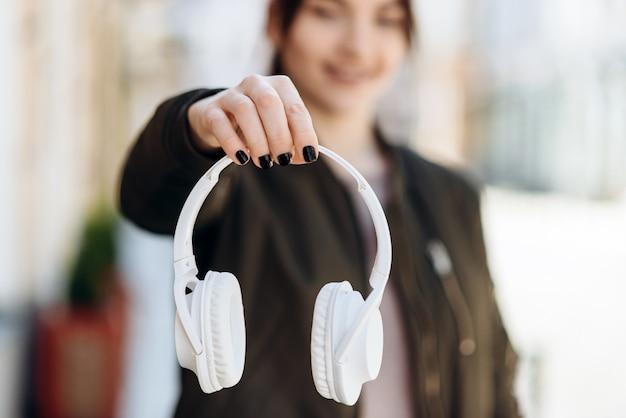 Na rozmytym tle dziewczyna jest wyraźnie widoczna jako ręka trzymająca słuchawki