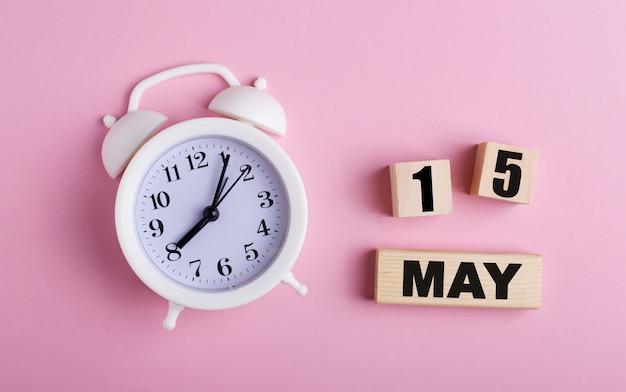 Na różowej powierzchni biały budzik i drewniane kostki z datą 15 maja