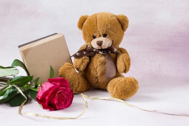 Na różowym tle jasnoróżowa róża, zabawkowy miś i pudełko na prezent