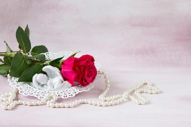 Na różowym tle jest jasnoróżowa róża, perłowe koraliki i figura anioła