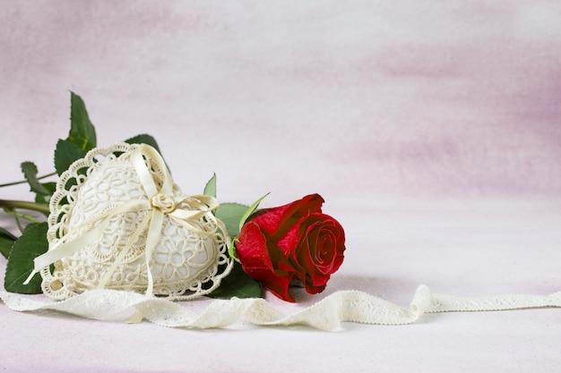 Na różowym tle jest jasnoróżowa róża, serce z koronki i wstążki