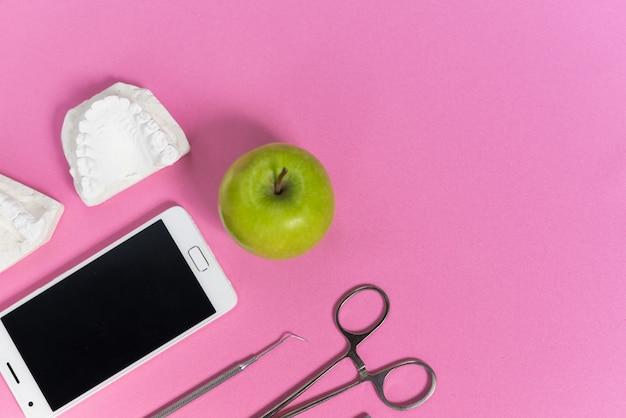 Na różowym tle jest telefon, jabłko i instrumenty dentystyczne