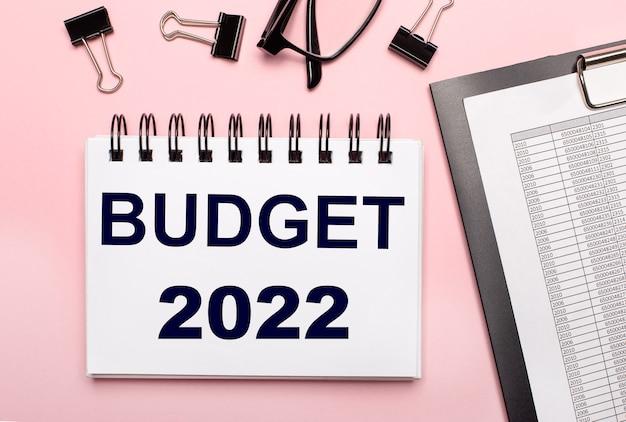 Na różowym tle raporty, czarne spinacze, okulary i biały zeszyt z napisem budżet 2022.