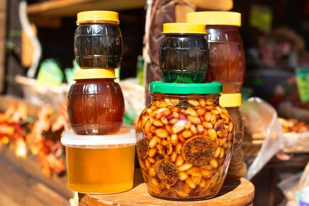 Na rynku egzotycznym miód z orzechami i figami sprzedawany jest w słoikach. jasny ciemny złoty. bazar