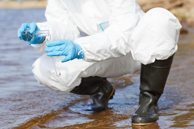 Na rysunku w zbliżeniu przedstawiono chemika w ochronnej odzieży roboczej oraz rękawiczkach trzymających kolbę i badającego wodę w rzece