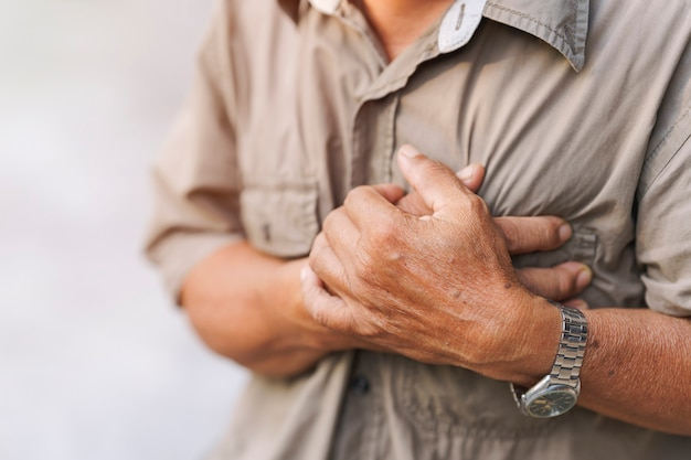 Na rysunku w zbliżeniu przedstawiono dłoń starszego mężczyzny, która bolała w klatce piersiowej. pojęcie choroby serca.