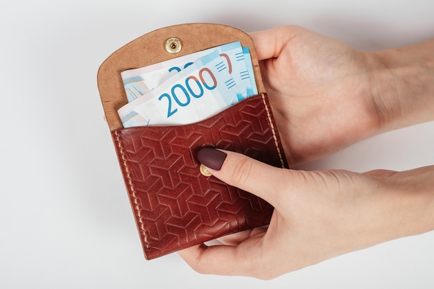 Na rysunku w zbliżeniu przedstawiono dłonie kobiety wkładającej do torebki banknot tysięcy rubli.