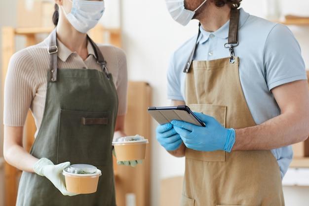 Na rysunku w zbliżeniu przedstawiono dwie osoby w maskach i rękawiczkach ochronnych korzystających z komputera typu tablet w pracy przy dostawie żywności
