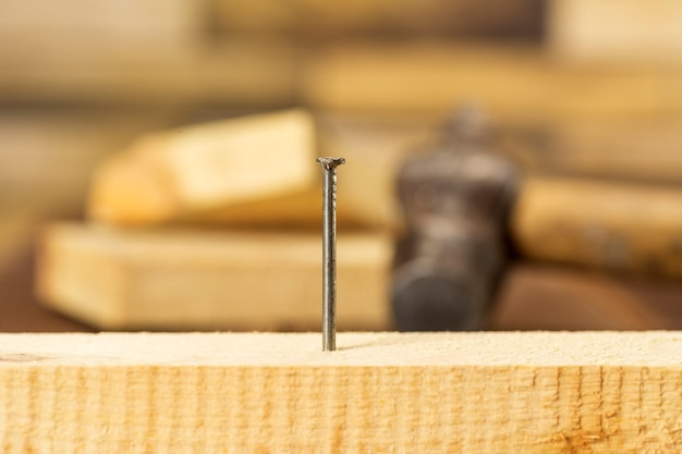 Na rysunku w zbliżeniu przedstawiono jeden gwóźdź wbity w drewnianą deskę