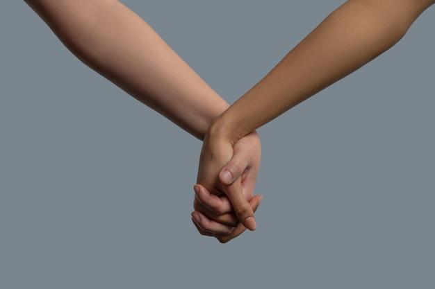 Na rysunku w zbliżeniu przedstawiono ludzi o jasnej i ciemnej karnacji trzymających się za ręce