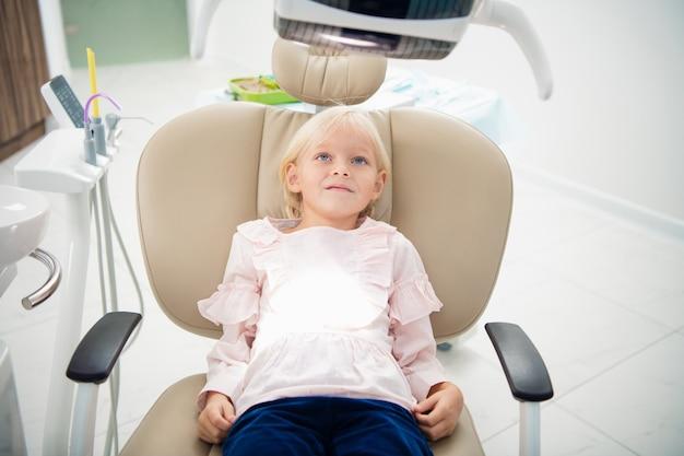 Na rysunku w zbliżeniu przedstawiono małą dziewczynkę czekającą w gabinecie stomatologicznym na badanie zębów.
