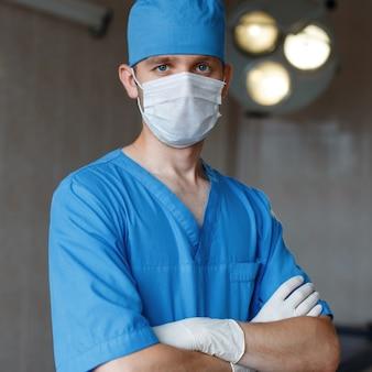 Na sali operacyjnej stoi młody chirurg w niebieskim mundurze, w białej masce medycznej w gumowych rękawiczkach