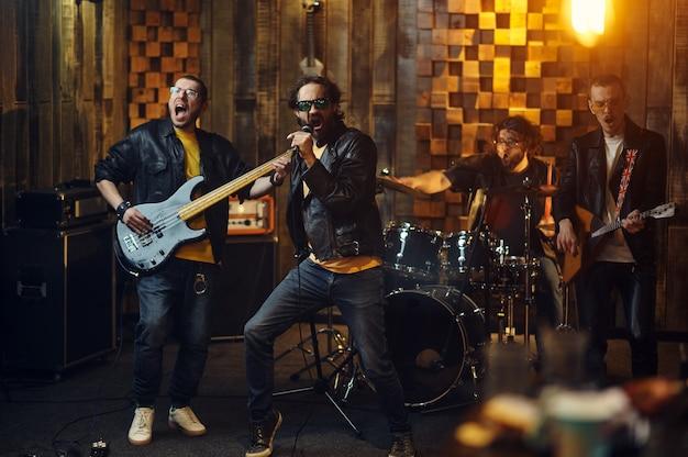 Na scenie występują brutalni artyści, muzyka i piosenki. występ zespołu rockowego lub powtórka w garażu, mężczyzna z instrumentem muzycznym, dźwięk na żywo
