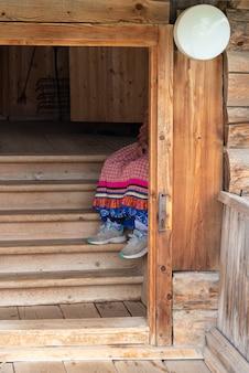 Na schodach chaty siedzi babcia ubrana w rosyjskim stylu ludowym i w nowoczesnych tenisówkach