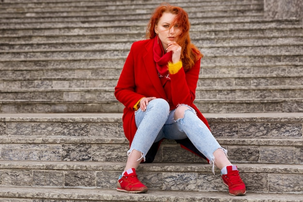 Na schodach na zewnątrz siedzi miła młoda kobieta z rudymi włosami, w czerwonym płaszczu i dżinsach