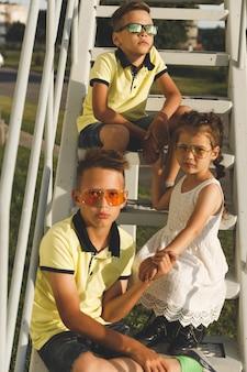 Na schodach siedzą dwaj bracia i siostra.