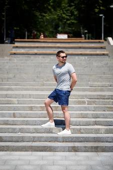 Na schodach stoi przystojny mężczyzna w koszulce i szortach. facet w okularach przeciwsłonecznych