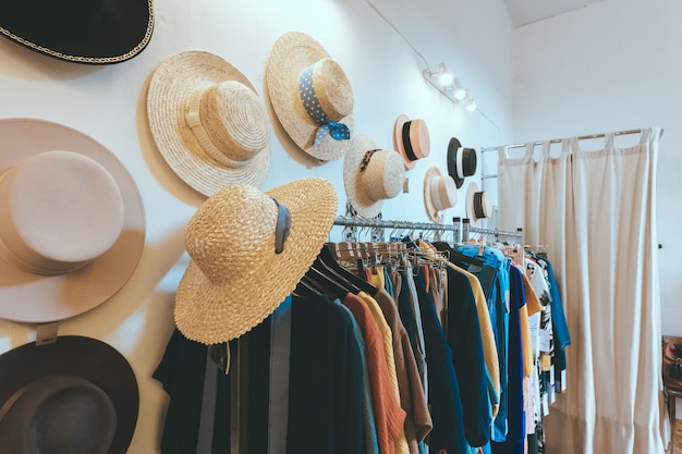 Na ścianie wisi salon wystawowy z odzieżą damską i letnimi słomkowymi kapeluszami. wieszak na stojaki z kolorowymi strojami. nowoczesne minimalistyczne wnętrze
