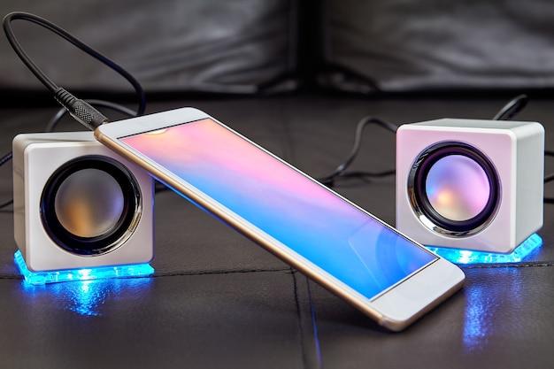 Na siedzisku sofy znajdują się dwa głośniki z niebieskimi diodami led, które są połączone ze smartfonem za pomocą kabla.