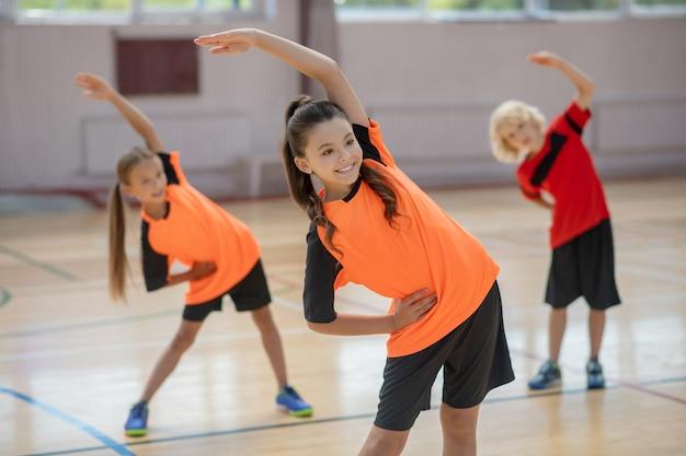 Na siłowni. trójka dzieci wyginających się w prawo na siłowni