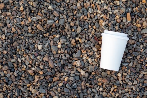 Na skalistym brzegu leży biały papierowy kubek z kawą lub herbatą. kubek gorącego napoju na kamyku. piękne skaliste tło. wolne miejsce na kopię.