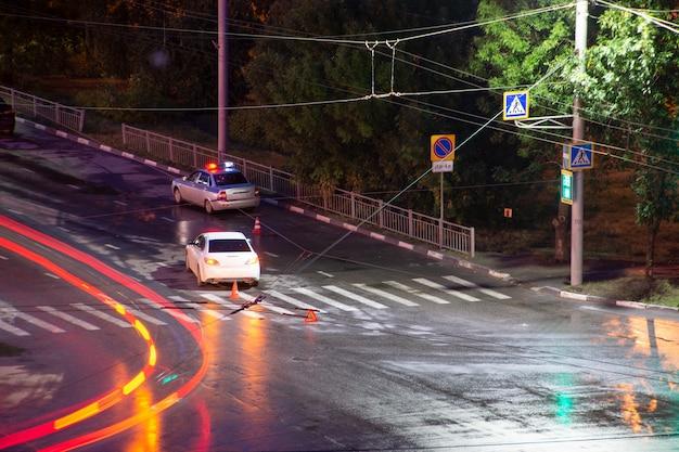 Na skrzyżowaniu w nocy kierowca zgwałcił i powalił pieszego. policja przygotowuje wypadek drogowy. wykroczenie drogowe. samochód inspektora policji z migającymi światłami awaryjnymi.
